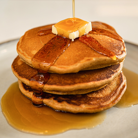 Gingerbread Pancake stack with butter and poured maple syrup