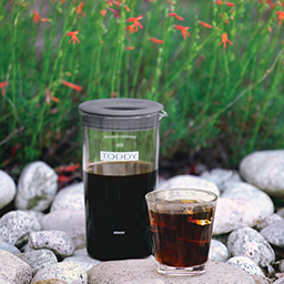 Toddy Artisan small batch cold brewer with coffee and glass of cold brew coffee on rocks outside by flowers