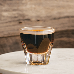 Glass of cold brew being served hot in tumbler on marble tabletop