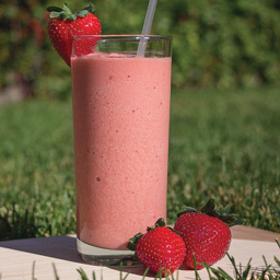 Toddy frappe with strawberries sitting on an outdoor table