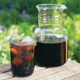 Toddy cold brew coffee extract in mason jar next to Toddy cold brew system
