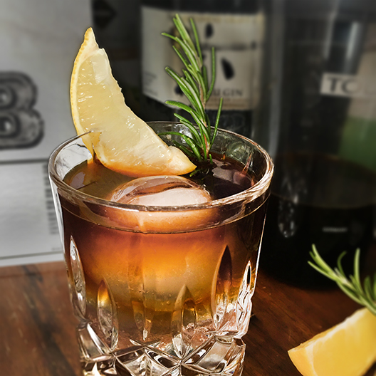 Cold Brew and Tonic in a glass with lemon and rosemary garnishes