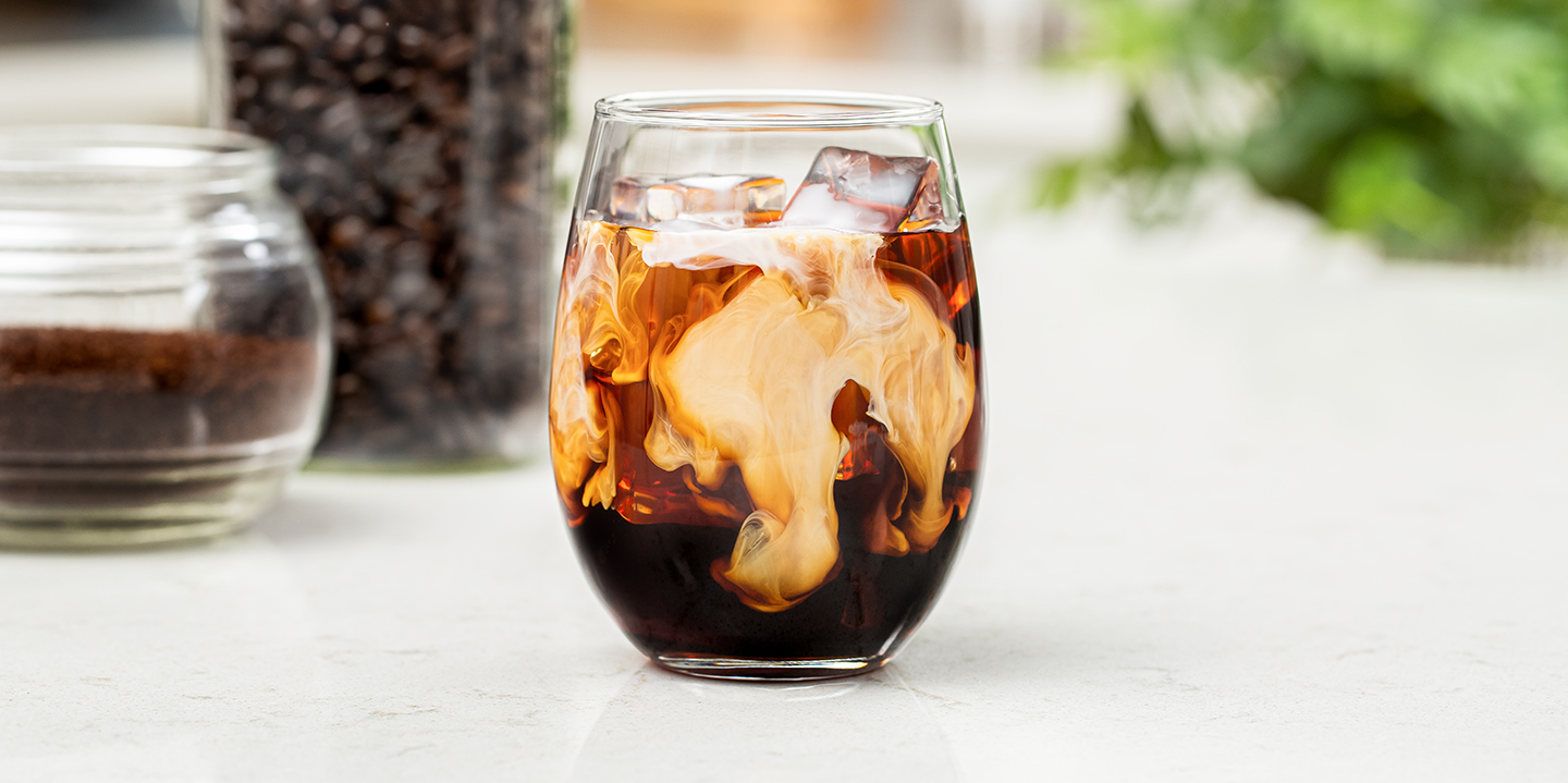 cold brew coffee with cream served over ice in a glass on counter