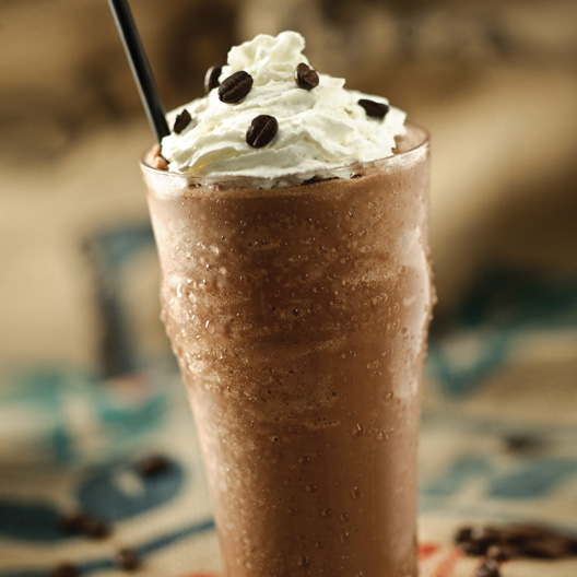 a large glass of frappe a la Toddy served wit whipped creme and espresso beans to top
