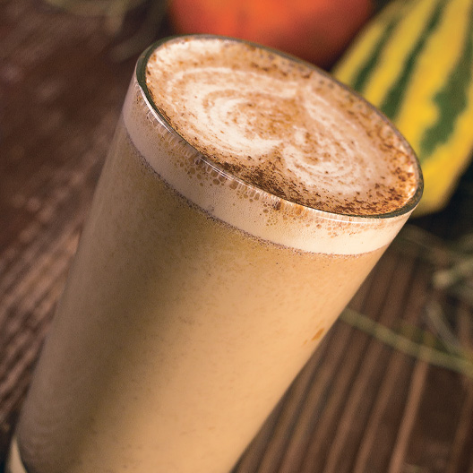 a clear glass of pumpkin pie served with steamed milk on top in decorative pattern and sprinkled with spice for additional flavor