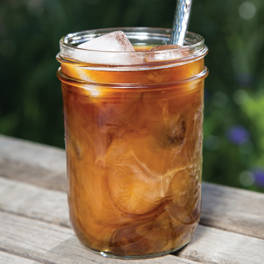a glass of thai iced coffee served in a mason jar